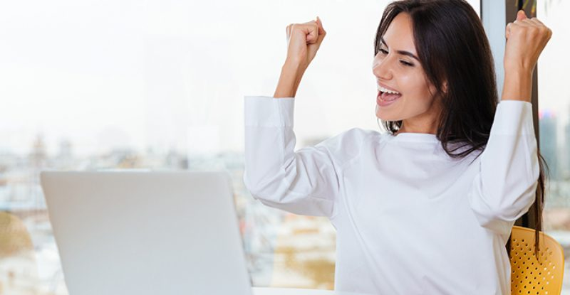 Cheerful successful young businesswoman with laptop shouting and celebrating success in office