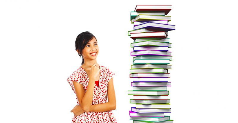 Young Student Smiling at Books to Read